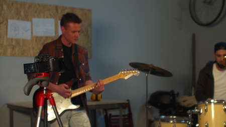 A group of two guitarists and a drummer play rock in their garage