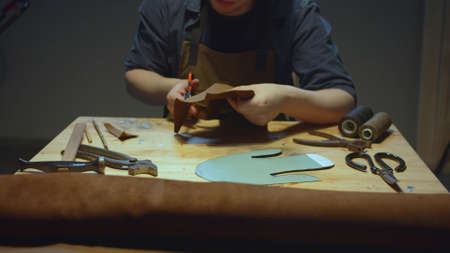 Young man carefully cuts a piece of material with scissors