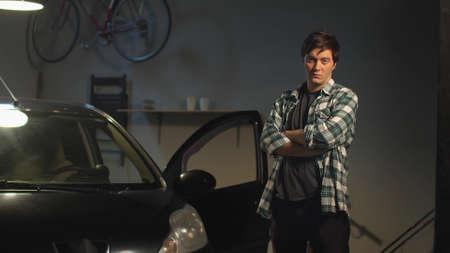 A man poses near his car in a garage. View