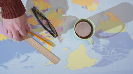 A man removes stationery, a mug of coffee, glasses and a map from the table