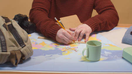 A man draws on a map on a ruler. Close up