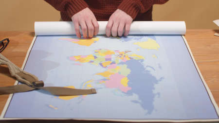 The cartographer rolls a map of the world and pulls out paper and pen 写真素材