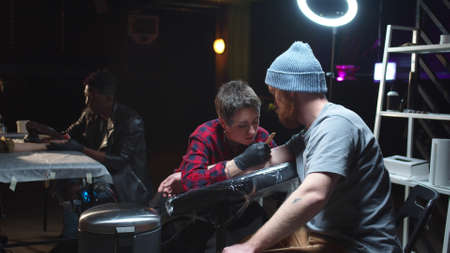 Tattoo artist stuffs a tattoo. Customers are waiting in the background Imagens