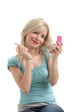 A blonde girl with red lips doing make up and smiling to camera
