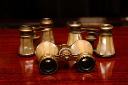 Three binoculars on a brown wood desk in old style photo