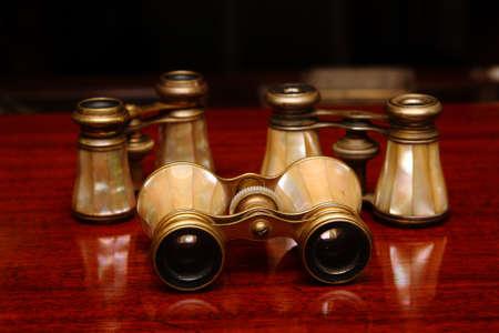 Three binoculars on a brown wood desk in old style photo