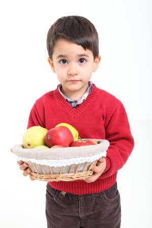 Child bringind basket fruit on white background photo