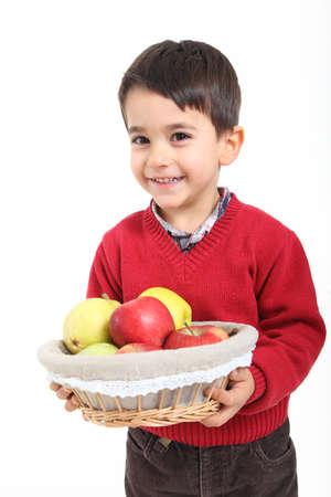 Child bringind basket fruit on white background