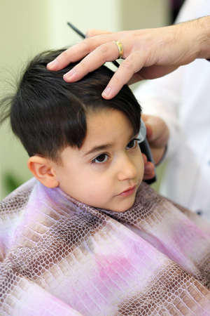 A lovely child in the hairdresser salon cutting his hair photo