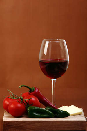 Red wine on brown background with cheese and vegetables photo