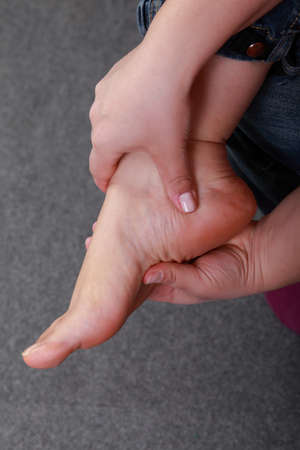 Hand self massage on a tired foot photo