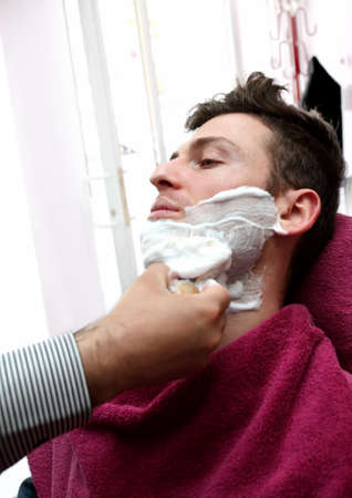 Young adult at barber shop for shaving photo