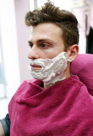 Young adult at barber shop for shaving Standard-Bild