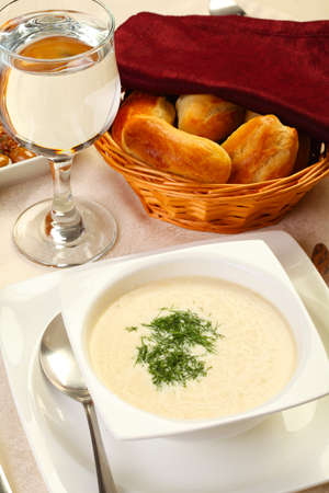 restaurant cream soup with bread and water glass photo