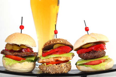 Three hamburgers on plate with glass of beer