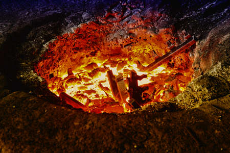 ferrous foundry: Melting iron pieces in a furnace hole Stock Photo