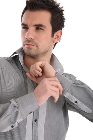 Handsome young man in shirt closing bottons Standard-Bild