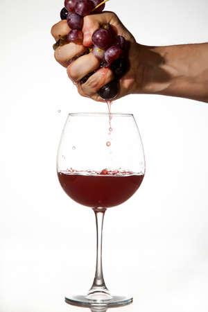 Hand drückte Trauben-Saft in einem Glas Rotwein zu machen Standard-Bild - 25984260