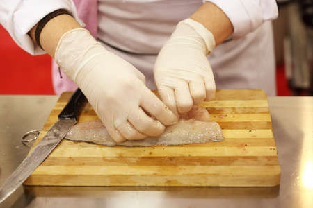 A chef is preparing and cutting a fresh fish photo