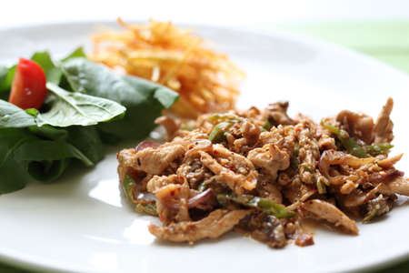 Chicken cooked with onions and peppers served with french fries Standard-Bild