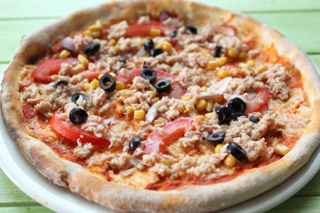 A fresh pizza with tuna fish in ambient light