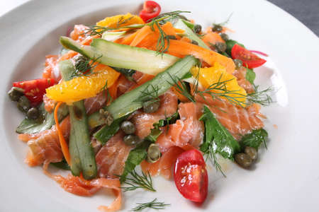 An healthy salmon salad dish served in ambient light