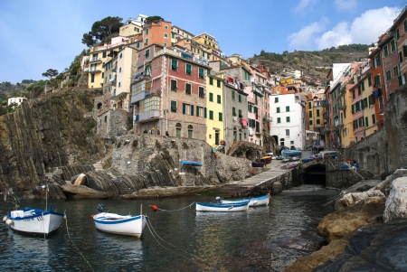 view from the sea of the village of Riomaggiore with the characteristic houses climbing the mountain photo