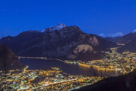 padania: Night view of Lecco city on Lake Como