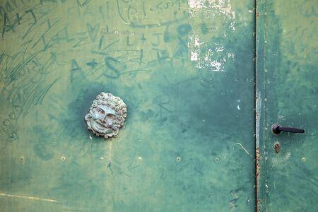 green door: Green door with mask decoration