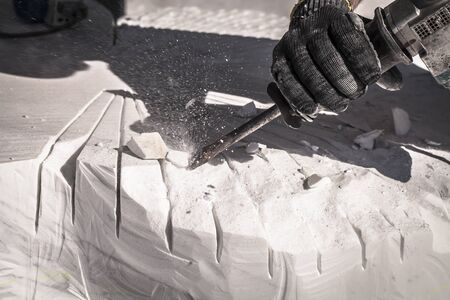 Artist sculpting marble with pneumatic hammer