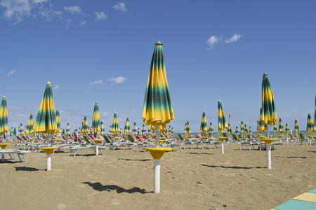 Strandparasols met ligstoelen aan het einde van het zomerseizoen