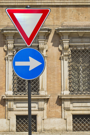 one lane road sign: Give way and right arrow direction signals with ancient italian military accademy as background