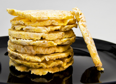 pile of rice and corn crakers on a black dish. for vegetarian and healthy food concept Archivio Fotografico
