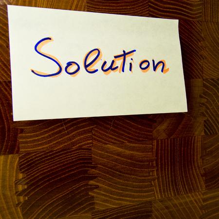 木製パネルに取り付けられた黄色のポストに書かれた単語ソリューション - 概念的な使用のために