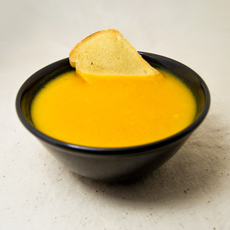 delicious pumpkin pured soup with potatoes and zwiebacks bread slices. for vegetarian, vegan and healthy concept