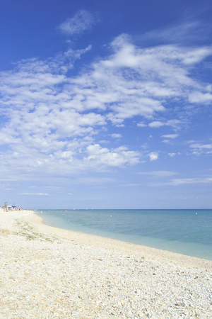 beach of marotta in the italian region of marche during summer with parasols and clouds Stock Photo