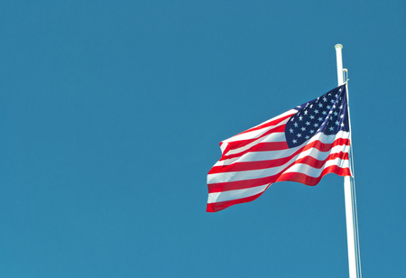 usa flag waving in the wind with blue sky as background. Stock Photo