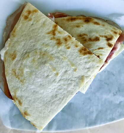 italian piadina with ham and squacquerone cheese. Traditional  regional flatbread food products of Italy of the Emilia-Romagna Region. 版權商用圖片