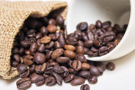 roasted coffee beans with raw textile and white porcelain coffee cup