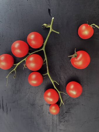 red pachino tomatoes grape on a bòack wooden background. Italian protected geographical indication product from Sicily