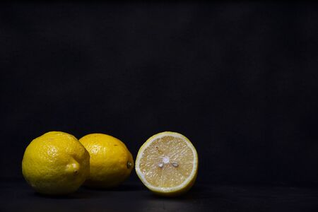 yellow lemons on a black wooden background from biologic agriculture.