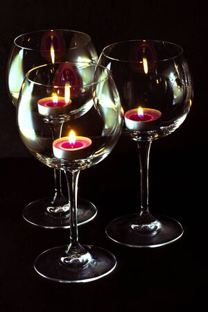 three candels tealights in wine glasses. romantic atmosphere and spa concepts Standard-Bild