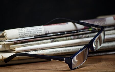 folded pile newspapers with a pair of blue reading glasses on it. free information and press concept