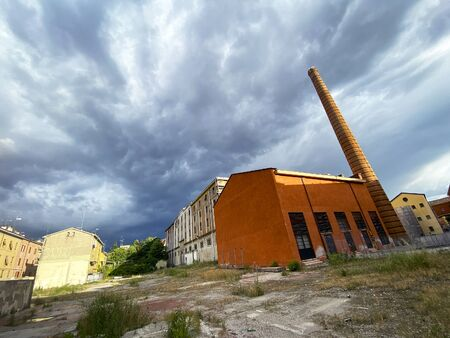 old ababdoned urban industrial complex with high chimney.partially recovered. concept for loss of job, working contitions