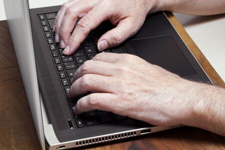 male hands typing on a laptop computer keybord. business, studyng, smart work concepts Imagens