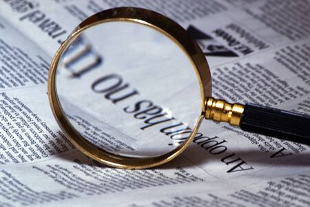 old style magnifying glass lens and newspaper. concept for fact checking, politics Imagens