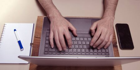 Caucasian male hands typing on a laptop pc keybord with mobile phone and squared block noted. Working concept