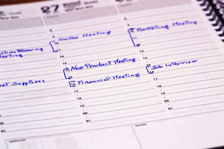 scheduling meeting time on a notepad to fix a business meeting. concept for business, job applications Imagens