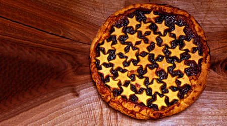 homemade plum jam tart pie on a wooden chopping board with stars shortcrust pastry decorations. Food concept