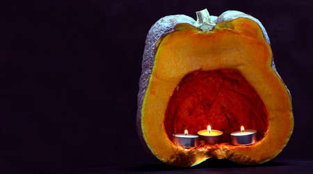orange pumpkin and three candle lights. concept for halloween decoration